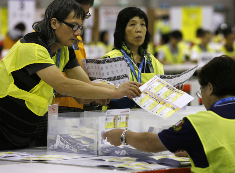 Electoral officers count ballots at the central ballot counting station after legislative elections in Hong Kong, Monday, Sept. 10, 2012. Hong Kong voters cast ballots in legislative elections Sunday that will help determine the eventual shape of full democracy that Beijing has promised the former British colony. (AP Photo/Kin Cheung)