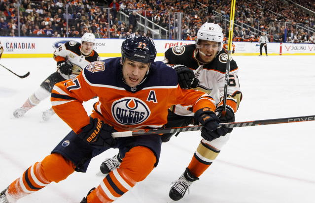 Anaheim Ducks' Rickard Rakell (67) and Edmonton Oilers' Milan Lucic (27) race to the puck during the second period of an NHL hockey game Saturday, Feb. 23, 2019, in Edmonton, Alberta. (Jason Franson/The Canadian Press via AP)