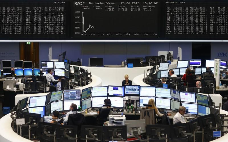 Traders sit at their desks in front of the DAX board at the Frankfurt stock exchange, Germany, June 29, 2015. REUTERS/Ralph Orlowski/Files