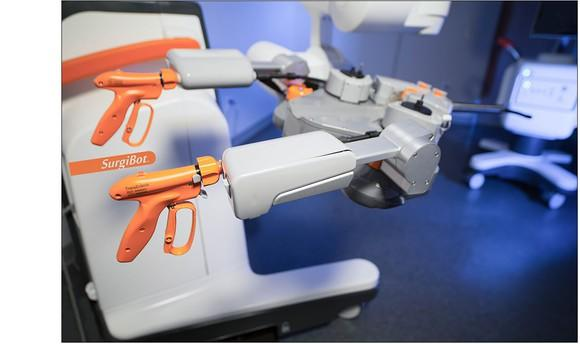 SurgiBot surgical system, with orange triggers for surgeons to use and a larger apparatus for performing surgery.