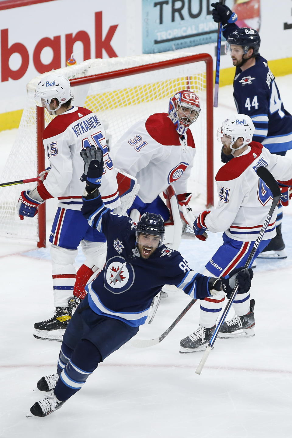 Winnipeg Jets' Mathieu Perreault (85) celebrates a goal by Derek Forbort, not seen, against Montreal Canadiens goaltender Carey Price (31) during the third period of Game 1 of an NHL hockey Stanley Cup second-round playoff series Wednesday, June 2, 2021, in Winnipeg, Manitoba. (John Woods/The Canadian Press via AP)