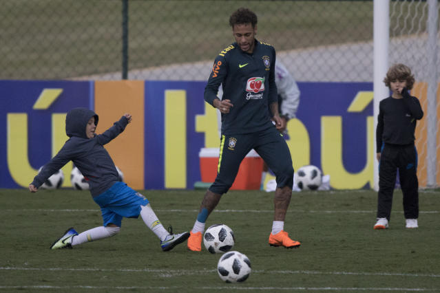 Brazil's Neymar plays with his son Davi Lucca, left, and one of his son's friends after a practice session of the Brazilian national soccer team ahead the World Cup in Russia, at the Granja Comary training center In Teresopolis, Brazil, Friday, May 25, 2018. (AP Photo/Leo Correa)