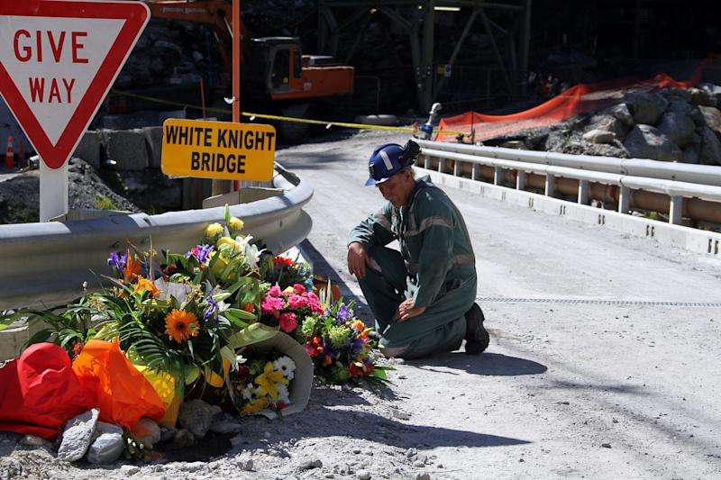 FILE - In this Nov. 29, 2010 file photo, a miner lays down flowers at White Knight Bridge near the entrance to the Pike River mine where 29 miners died, in Greymouth, New Zealand.  Australian drilling company VLI Drilling  pleaded guilty Tuesday, July 31, 2012,  to three health-and-safety violations in connection with the 2010 coal mine disaster in New Zealand. (AP Photo/NZPA, Ross Setford, File) NEW ZEALAND OUT