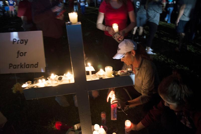 A cross adorned with lit candles was one of many seen at Thursday night's vigil.