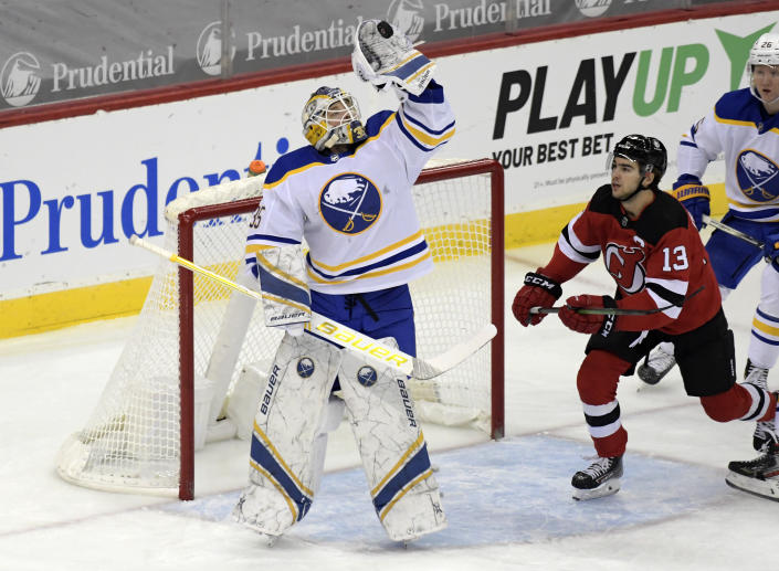 Buffalo Sabres goaltender Linus Ullmark (35) gloves the puck as New Jersey Devils center Nico Hischier (13) looks on during the first period of an NHL hockey game Tuesday, Feb. 23, 2021, in Newark, N.J. (AP Photo/Bill Kostroun)