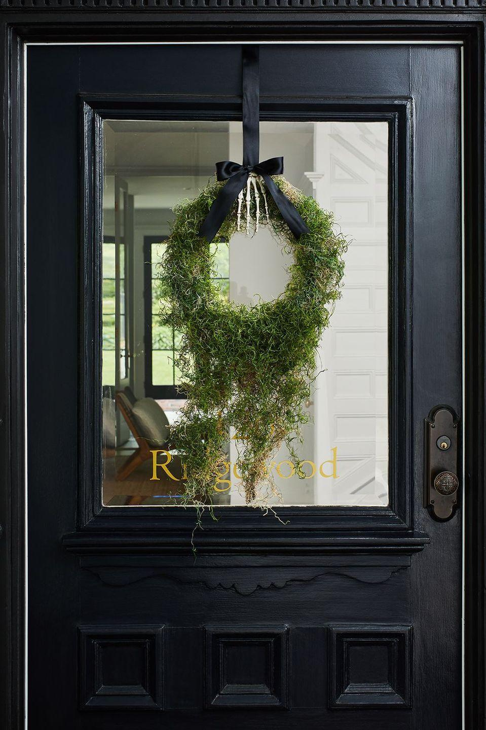 <p>Cover a wreath form with dripping moss and suspend from your front door with a spooky skeleton hand and black ribbon for an elegantly understated creepy decoration.</p>