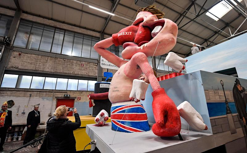 People watching a satiric carnival float depicting the Brexit during a preview in a hall in Cologne, Germany, Feb. 26, 2019. (AP Photo/Martin Meissner)