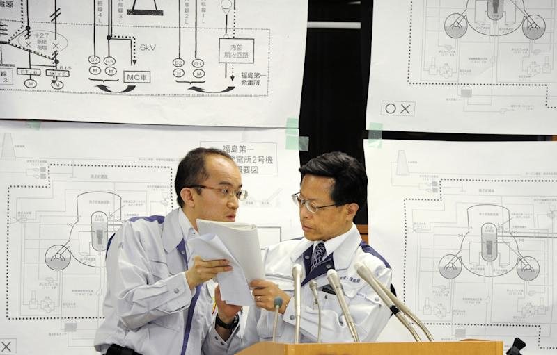 Nuclear and Industrial Safety Agency spokesman Hidehiko Nishiyama, right, huddles with his aide during a press conference on the crippled Fukushima Dai-ichi nuclear complex, in Tokyo on Friday March 25, 2011. (AP Photo/Kyodo News) JAPAN OUT, MANDATORY CREDIT, NO LICENSING IN CHINA, HONG KONG, JAPAN, SOUTH KOREA AND FRANCE