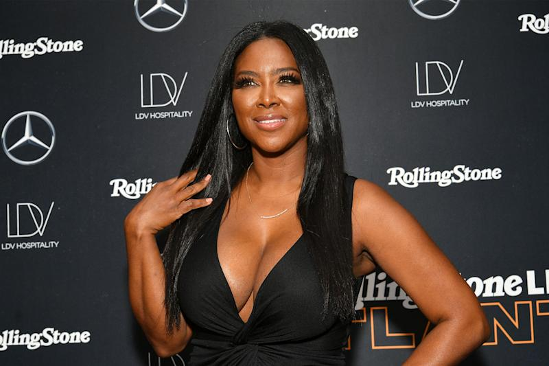 Kenya Moore looks dazzling in black body-con dress that leaves nothing to imagination in her cleavage area.
