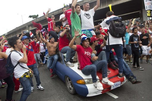 Costa Rica soccer fans on a car painted in the colors of the nation's flag celebrate their team's victory over Greece at a Brazil World Cup round of 16 game in San Jose, Costa Rica, Sunday, June 29, 2014. Costa Rica won a penalty shootout 5-3 after the match ended 1-1 following extra time. (AP Photo/Esteban Felix)