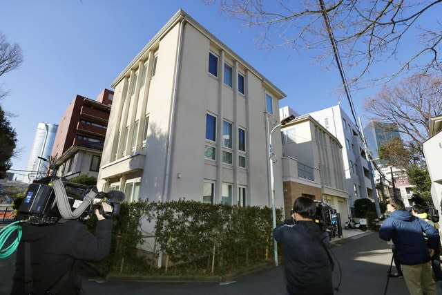 Journalists wait outside former Nissan chairman Carlos Ghosn's residence before a raid in Tokyo