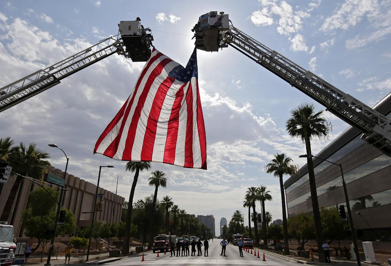 The Phoenix Fire Department hangs a flag in preparation for procession of 19 hearses that will drive through Phoenix, Ariz. Sunday, July 7, 2013. The elite crew of firefighters were overtaken by the out-of-control blaze as they tried to protect themselves from the flames under fire-resistant shields. (AP Photo/Chris Carlson)