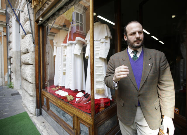 Shop owner Lorenzo Gammarelli walks by the shop window where three sets of papal outfits - small, medium and large sizes - which will be sent to the Vatican for the new pope, are displayed, in Rome, Monday, March 4, 2013. For over a half century the Gammarelli family has produced the pope robes in three different sizes that are delivered before the conclave meets, in order to fit the newly elected popes. (AP Photo/Andrew Medichini)