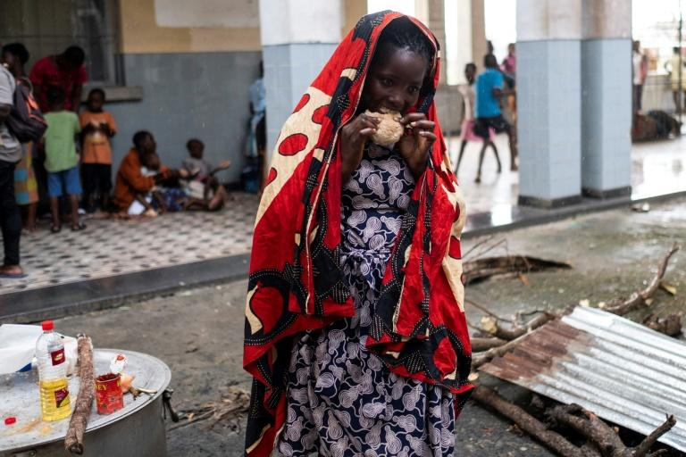A woman eats at an emergency foodbank in Beira, Mozambique