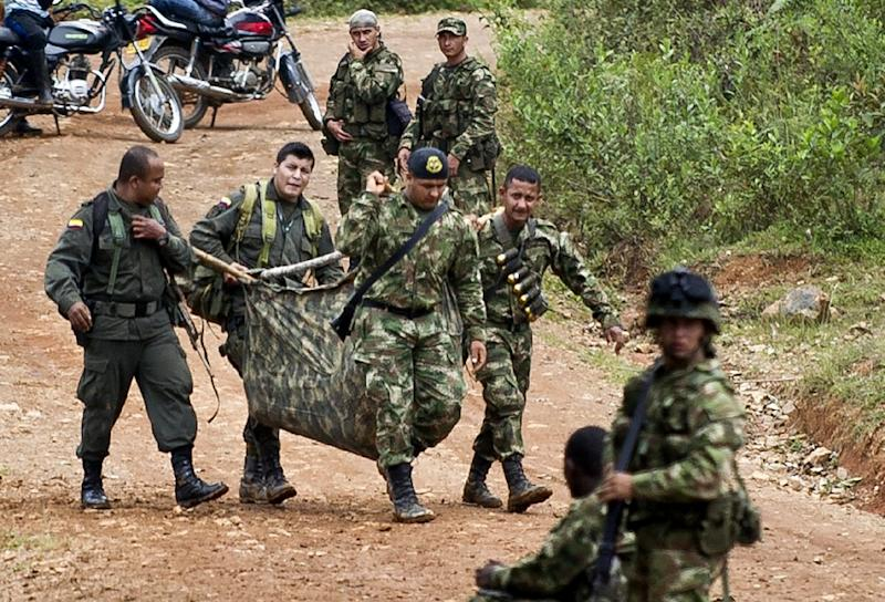 Colombian soldiers carry equipment of one of ten soldiers killed by FARC guerrillas, in the department of Cauca on April 15, 2015 (AFP Photo/Luis Robayo)
