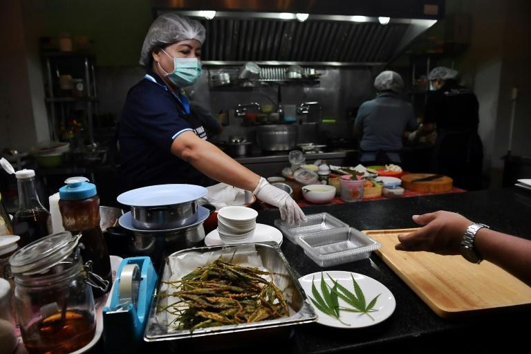 In the restaurant's bustling kitchen, a cook batters marijuana leaves and fries them to golden crispness, while another sprinkles them in a wok of minced meat with chili
