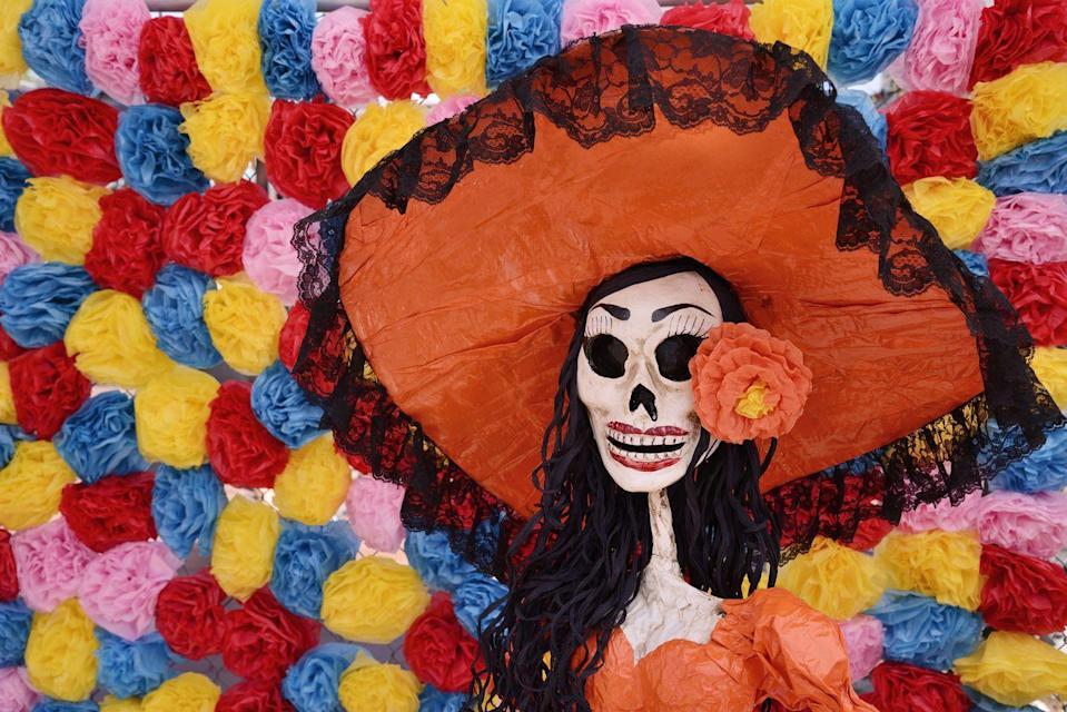"<p><a href=""https://dayofthedead.holiday/traditions/who-is-la-catrina"" rel=""nofollow noopener"" target=""_blank"" data-ylk=""slk:La Calavera Catrina"" class=""link rapid-noclick-resp"">La Calavera Catrina</a> originated from a 1913 etching by Mexican artist José Guadalupe Posada. The original depiction showed a skeleton in a large hat. Catrina was later given a body by Mexican painter Diego Rivera, who portrayed her as the central figure in his 1947 mural ""Sueño de una tarde dominical en la Alameda Central"" (""Dream of a Sunday Afternoon along Central Alameda""), which can be seen in the Diego Rivera Mural Museum in Mexico City. Catrina is a core part of any Dia de Muertos celebration and is honored in costumes, makeup, and other festive imagery.</p>"