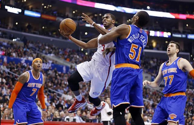 Los Angeles Clippers' Chris Paul (3) goes up to score past New York Knicks' Metta World Peace (51) while Carmelo Anthony, rear left, and Andrea Bargnani, rear right, stand by during the first half of an NBA basketball game in Los Angeles, Wednesday, Nov. 27, 2013. (AP Photo/Danny Moloshok)