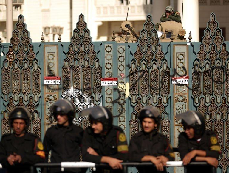 "Riot police guard the gates of the presidential palace in Cairo. Egypt's powerful military has demanded the Islamist-led government and political foes start dialogue and warned it will not permit events to take a ""disastrous"" turn"