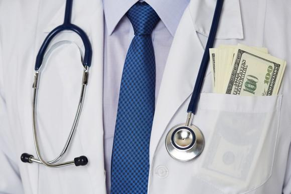 Closeup of physician's lab coat, stethoscope, and blue tie, with hundred dollar bills in his pocket.