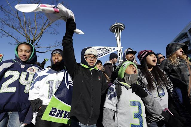 Seattle Seahawks fans cheer as they wait for the Seahawks' Super Bowl victory parade to begin Wednesday, Feb. 5, 2014, in Seattle. The Seahawks beat the Denver Broncos 43-8 on Sunday. (AP Photo/Elaine Thompson)
