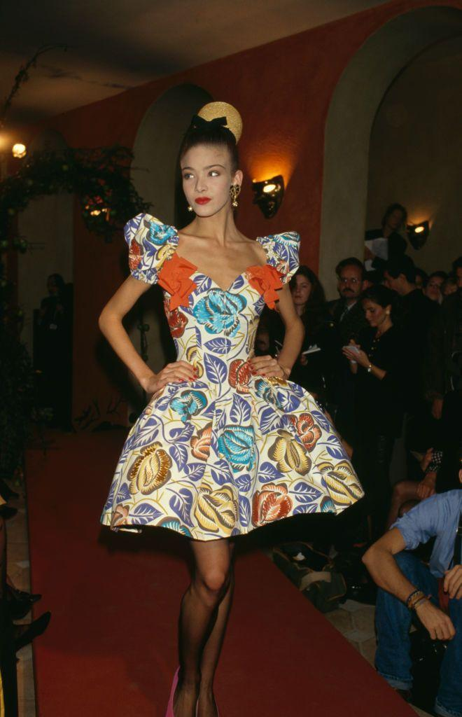 <p>A model, wearing a printed dress with a poof skirt and puff sleeves, walks the runway at Christian Lacroix's spring 1988 fashion show. </p>
