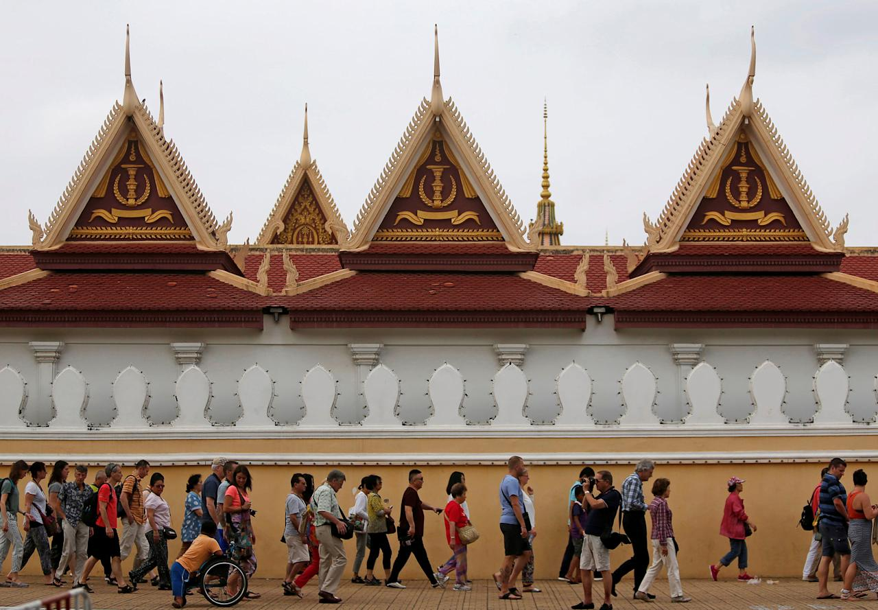 Tourists walk outside the Royal Palace in central Phnom Penh, Cambodia, April 19, 2018. REUTERS/Samrang Pring