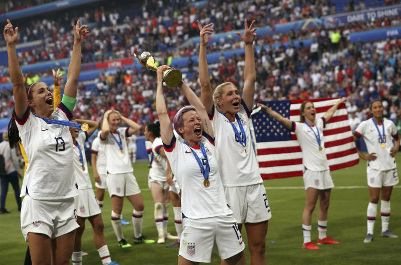 United States' Megan Rapinoe, center, holds the trophy as she celebrates with teammates after they defeated the Netherlands 2-0 in the Women's World Cup final soccer match at the Stade de Lyon in Decines, outside Lyon, France, Sunday, July 7, 2019. (AP Photo/Francisco Seco)
