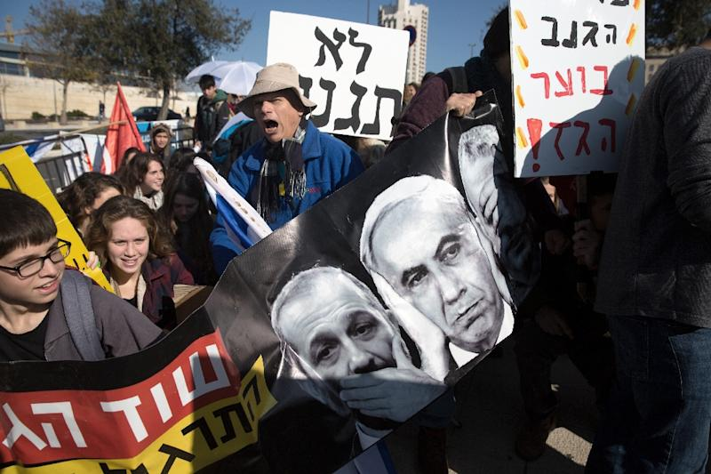 An Israeli protester holds a banner bearing a portrait of Israeli Prime Minister Benjamin Netanyahu on February 3, 2016 in front of the Supreme Court in Jerusalem where a hearing takes place on a contentious natural gas deal (AFP Photo/Menahem Kahana)