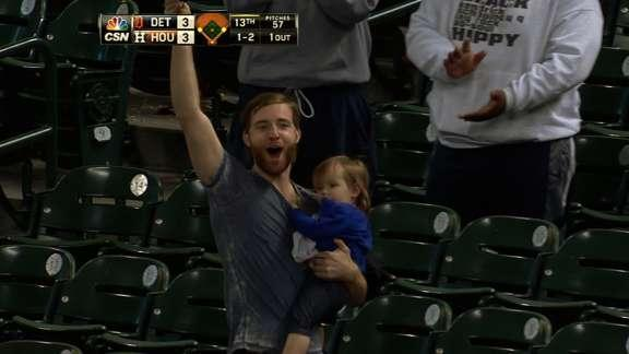 Fan holding a baby makes a sweet catch at Houston Astros game — with his cap (Video)