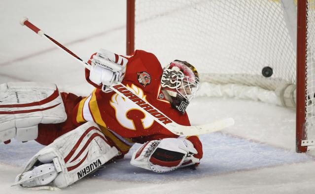 Calgary Flames goalie Joni Ortio, from Finland, looks back at a goal by the New York Islanders during the second period of an NHL hockey game Friday, March 7, 2014, in Calgary, Alberta. (AP Photo/The Canadian Press, Jeff McIntosh)