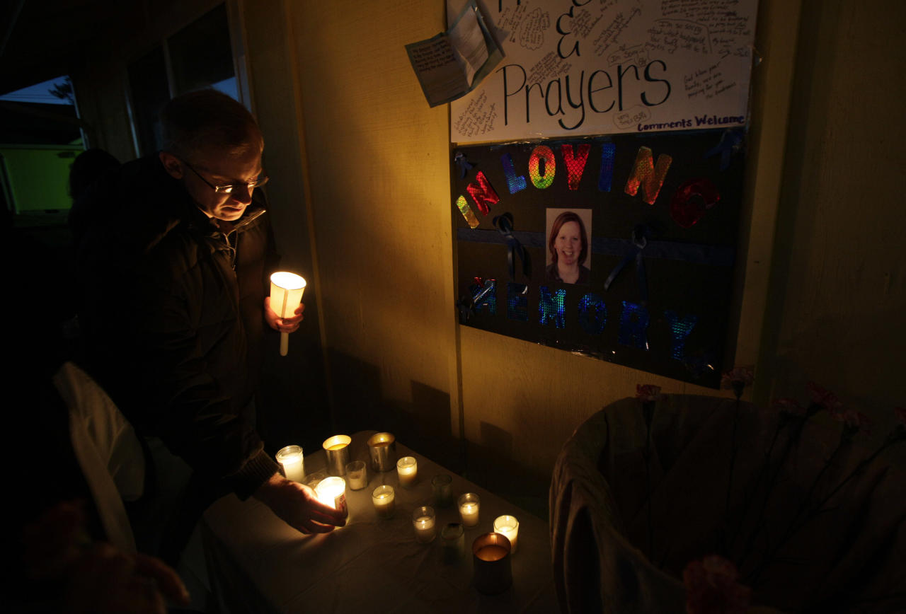 Peter Kritsch, the brother of slain park ranger Margaret Anderson, pictured on the poster at right, lights a candle in memory of his sister during an evening vigil for Anderson, Sunday, Jan. 8, 2012, in Eatonville, Wash. Anderson was killed by a gunman on Jan. 1, 2012, during a traffic stop where she worked at Mount Rainier National Park. (AP Photo/Ted S. Warren)
