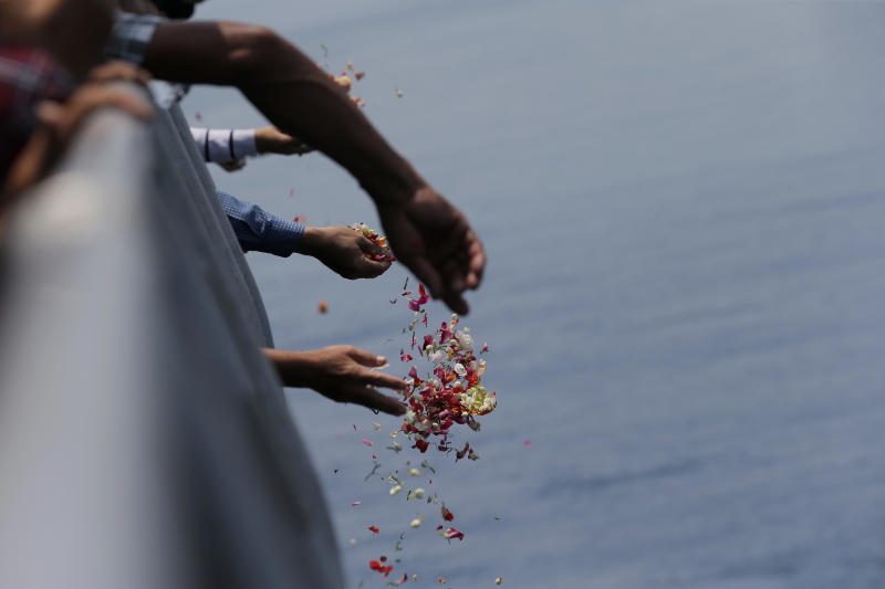 Relatives sprinkle flowers for the victims of the crashed Lion Air flight 610 from an Indonesia Navy ship in the waters where the airplane is believed to have crashed in Tanjung Karawang, Indonesia, Tuesday, Nov. 6, 2018. (AP Photo/Tatan Syuflana)