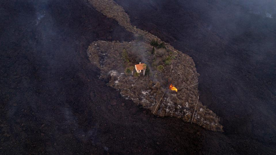 Sept. 20, 2021: In this photo provided by iLoveTheWorld, a house remains intact as lava flows after a volcano erupted near Las Manchas on the island of La Palma in the Canaries, Spain. A dormant volcano on a small Spanish island in the Atlantic Ocean erupted on Sunday, forcing the evacuation of thousands of people. Huge plumes of black-and-white smoke shot out from a volcanic ridge where scientists had been monitoring the accumulation of molten lava below the surface.