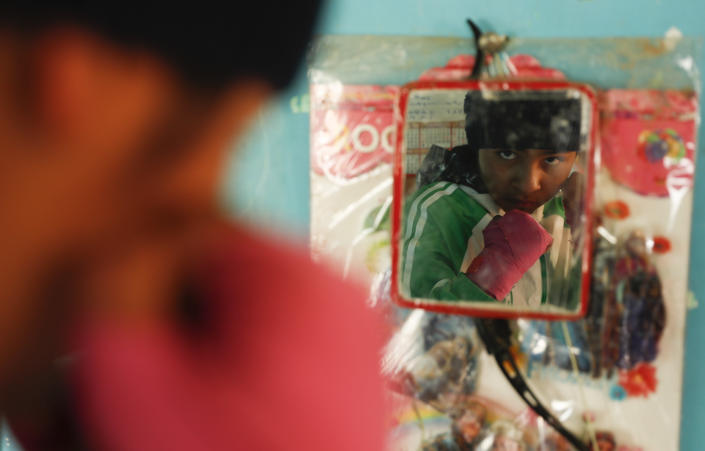 Gracce Kelly Flores, a 12-year-old boxer who goes by the nickname Hands of Stone, strikes a pose in the mirror hanging in her home's kitchen after her morning workout in Palca, Bolivia, early Thursday, June 10, 2021, amid the COVID-19 pandemic. At age 8, Flores defeated a 10-year-old boy, and with three national boxing medals under her belt, she dreams of reaching the women's boxing world championship. (AP Photo/Juan Karita)