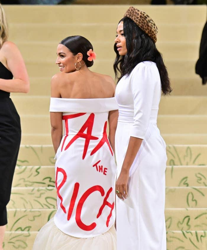 The New York congresswoman's white gown was designed by Aurora James, who joined AOC at the Met Gala. AOC also wore the statement on a red purse.