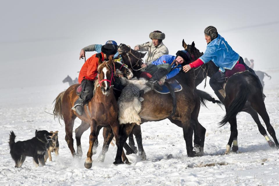 Riders compete during a kok boru, also called ulak tartysh, a traditional game in which players on horseback maneuver with a goat's carcass and score by putting it into the opponents' goal outside Tash-Dobo village, 15 kilometers (9 miles) south of Bishkek, Kyrgyzstan, Saturday, Dec. 12, 2020. The game has its origins in the distant past, when men went to hunt wolves which attacked their livestock, picking up running wolves from the ground and throwing them between each other almost playfully. Today, the game today requires teams to throw a dead sheep or goat into their opponent's well on the playing field. (AP Photo/Vladimir Voronin)