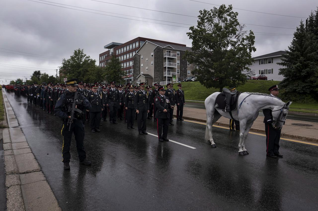 <p>Cost. Stefan Decourcey, right, leads the horse Grimsby who he co-owned with Cost. Sara Burns as they and other Fredericton police officers follow the hearses carrying Cost. Burns and Cost. Robb Costello during a regimental funeral in Fredericton on Saturday, Aug. 18, 2018. T (Photo from The Canadian Press/Darren Calabrese) </p>