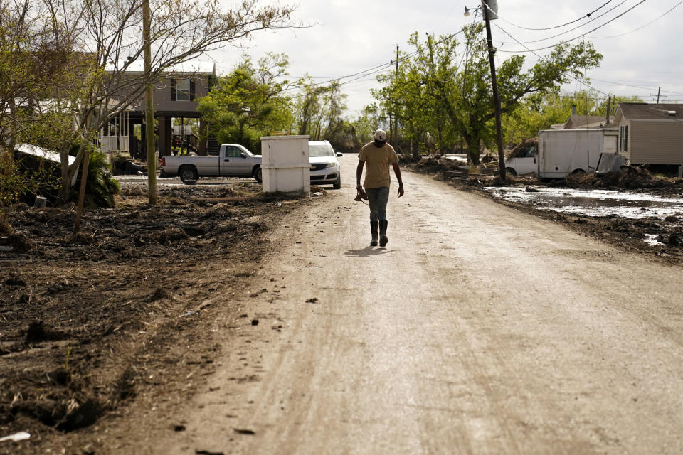 Kornell Davis walks down a road after trying to clean up his destroyed home, in Ironton, La., Monday, Sept. 27, 2021. A month after Hurricane Ida, small communities along Louisiana's southeastern coast are still without power or running water. Some residents have lost most of their possessions to the storm's floodwaters. (AP Photo/Gerald Herbert)