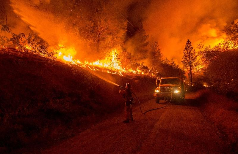 A firefighter douses flames from a backfire while battling the Butte fire near San Andreas, California, September 12, 2015 (AFP Photo/Josh Edelson)
