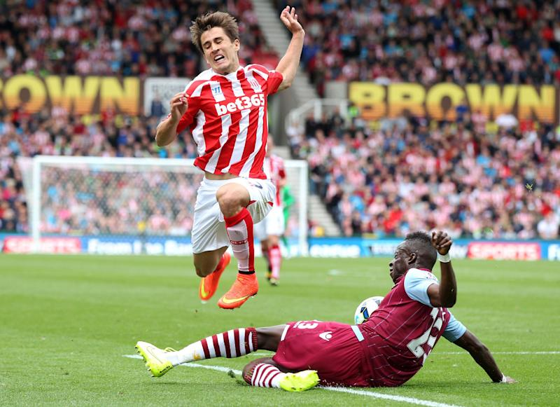Aston Villa's Aly Cissokho, right, and Stoke City's Bojan battle for the ball during their English Premier League soccer match at The Britannia Stadium, Stoke, England, Saturday, Aug. 16, 2014