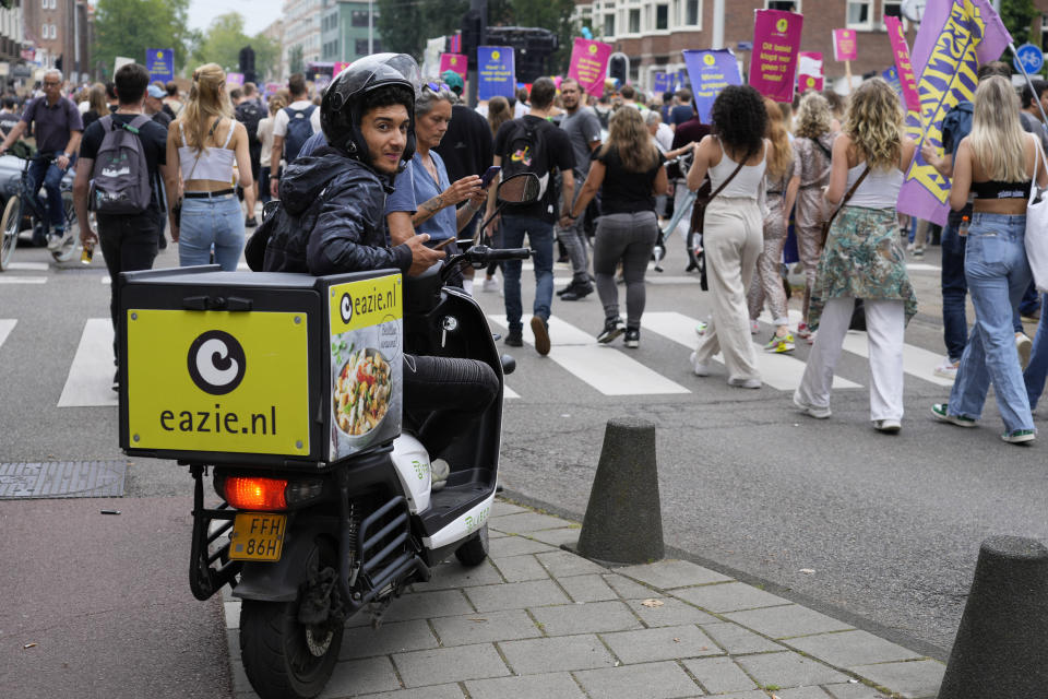 A food delivery person waits as thousands of fans of music festivals stage a protest in Amsterdam, Netherlands, Saturday, Aug. 21, 2021, against the government's COVID-19 restrictions on large-scale outdoor events. On Saturday, the festivals came to music fans as hundreds of performers and festival organizers held demonstration marches through six Dutch cities to protest what they argue are unfair restrictions that have forced the cancellation of summer festivals and other events. (AP Photo/Peter Dejong)