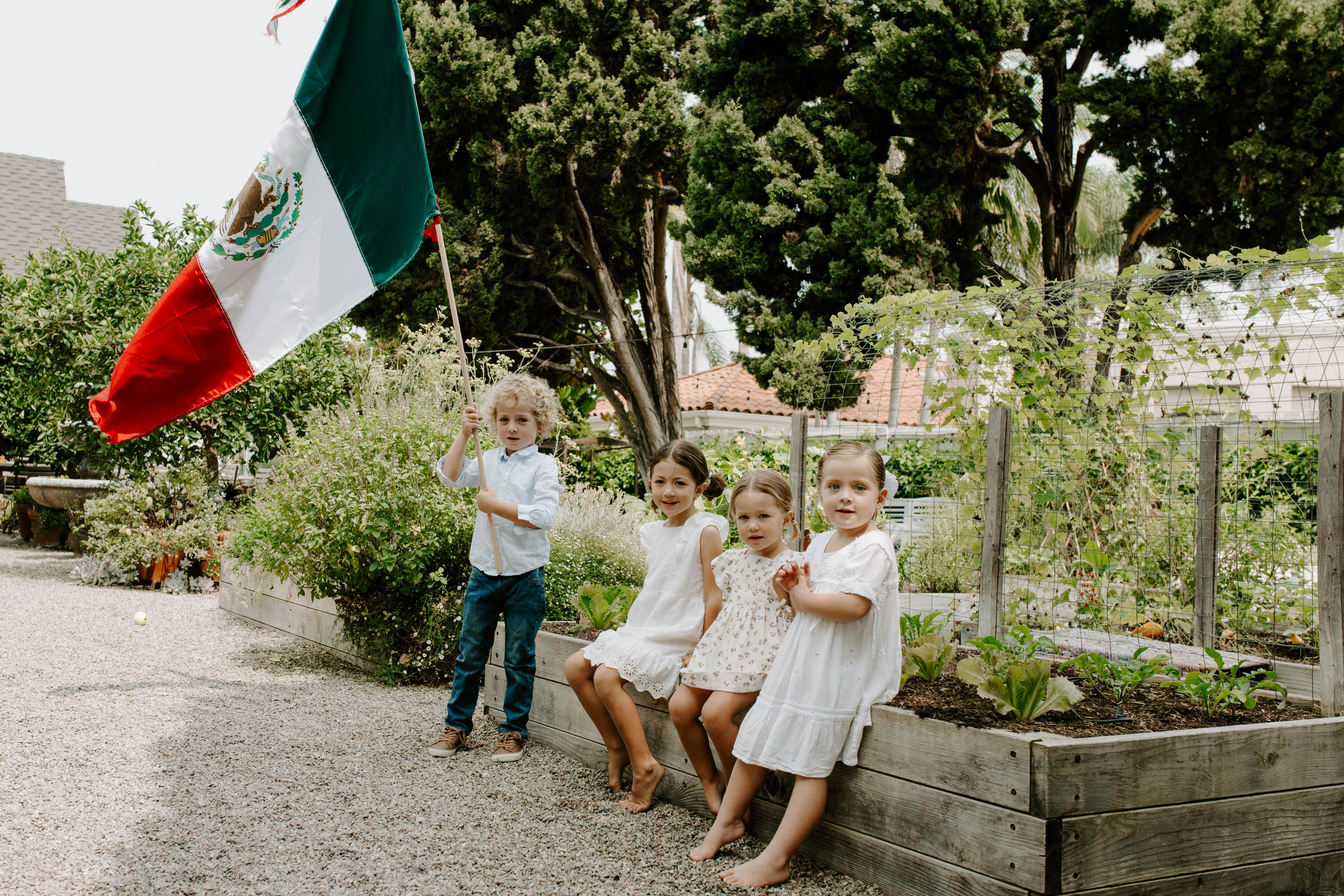 Children dressed for celebration pose with a Mexican flag in Valladolid's San Diego garden. (Photo: Cecilia Martin Del Campo)