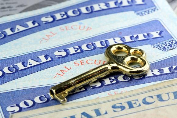 Social Security cards on a table with a gold key lying on top.