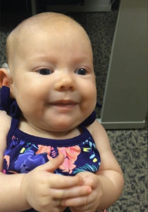 The three-month-old smiles when she realises she can hear her mother's voice. Credit: Caters
