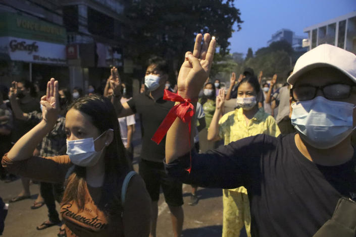 Anti-coup protesters flash three-fingered gesture, a symbol of resistance, during a rally outside their homes in downtown Yangon, Myanmar, Monday morning, March 22, 2021. (AP Photo)