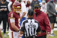 FILE - In this Sunday, Oct. 11, 2020 file photo, Washington Football Team head coach Ron Rivera and quarterback Kyle Allen talk to field judge Dale Shaw (104) during the first half of an NFL football game against the Los Angeles Rams in Landover, Md. The first game between 1-5 Washington and the 2-4 Dallas Cowboys since the name change is also the longtime NFC East rivals' first meeting with this bad a combined winning percentage since 2001. That was a 9-7 game kicker Tim Seder won with a 26-yard field goal as time expired after a collision with a horse on the field during warmups. (AP Photo/Steve Helber, File)