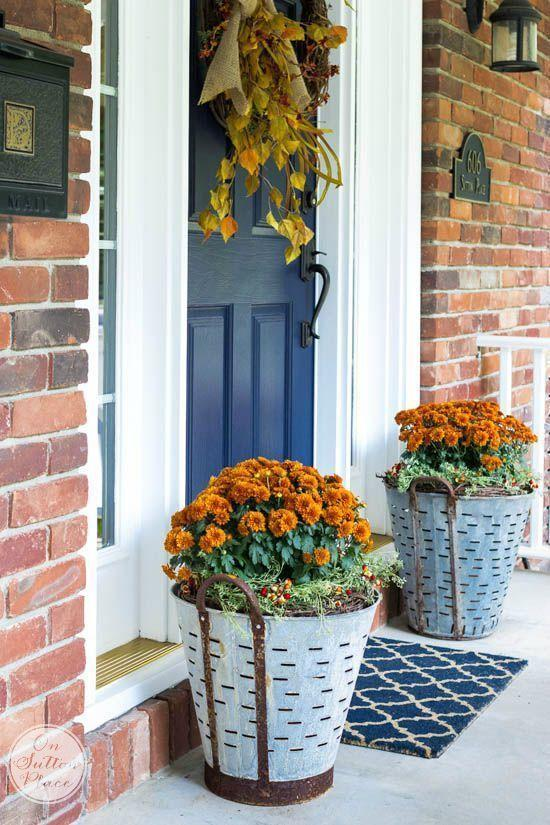 """<p>Just because summer's over doesn't mean you can't bookend your entryway with brightly colored blooms! These vintage """"olive buckets,"""" as they're called, are a beautiful way to showcase autumnal flowers of your choosing.</p><p><strong>See more at <a href=""""http://www.onsuttonplace.com/2015/09/fall-mums-in-olive-buckets/"""" rel=""""nofollow noopener"""" target=""""_blank"""" data-ylk=""""slk:On Sutton Place"""" class=""""link rapid-noclick-resp"""">On Sutton Place</a>.</strong></p><p><strong><a class=""""link rapid-noclick-resp"""" href=""""https://go.redirectingat.com?id=74968X1596630&url=https%3A%2F%2Fwww.walmart.com%2Fsearch%2F%3Fquery%3Dgalvanized%2Bplanters&sref=https%3A%2F%2Fwww.thepioneerwoman.com%2Fhome-lifestyle%2Fdecorating-ideas%2Fg36732301%2Foutdoor-fall-decorations%2F"""" rel=""""nofollow noopener"""" target=""""_blank"""" data-ylk=""""slk:SHOP GALVANIZED PLANTERS"""">SHOP GALVANIZED PLANTERS</a></strong></p>"""