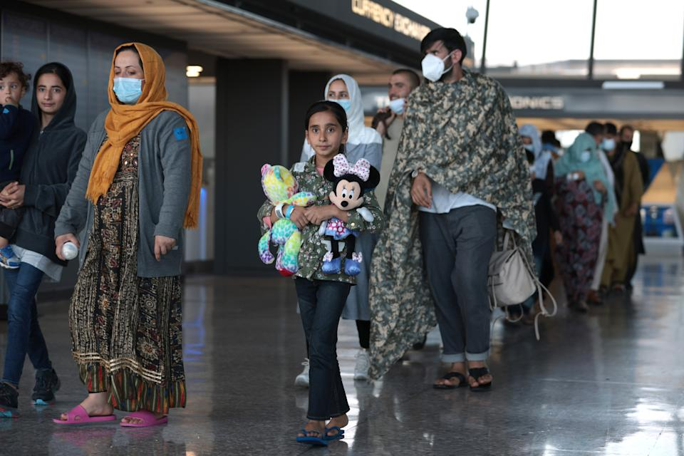 DULLES, VIRGINIA - AUGUST 25: A family of people evacuated from Afghanistan are led through the arrival terminal at the Dulles International Airport to board a bus that will take them to a refugee processing center on August 25, 2021 in Dulles, Virginia. According to the U.S. Department of Defense, five evacuation flights from Kabul, Afghanistan have landed at the Dulles Airport carrying 1,200 Afghan refugees in last day. The White House also announced that since August 14, the U.S. has evacuated and facilitated the evacuation of approximately 82,300 people on US military and coalition flights. (Photo by Anna Moneymaker/Getty Images)