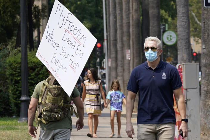 A person toting a sign from a demonstration against mandatory vaccinations passes a man wearing a face mask by the Capitol in Sacramento, Calif., Monday, Aug. 16, 2021. California is mandating COVID-19 vaccinations for all health care workers and will require state government and school staff to be vaccinated or regularly tested.(AP Photo/Rich Pedroncelli)